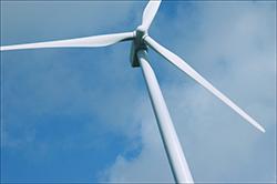 closeup of wind turbine against blue sky