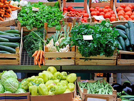 variety of vegetales in crates on racks at a farmers market